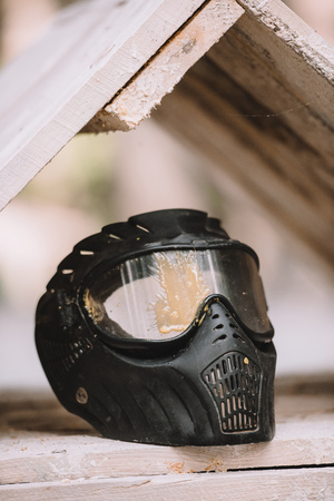 selective focus of protective mask covered by paintball splash outdoors