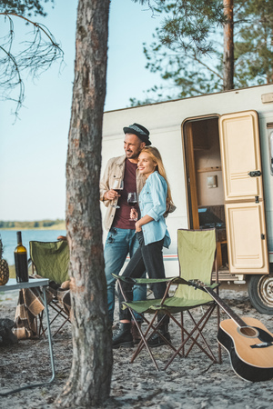 young couple with glasses of wine standing near campervan Banco de Imagens