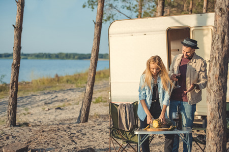 young woman cutting pineapple while man with glass of wine talking to her near trailer