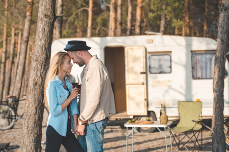 young couple touching the foreheads and holding glasses of wine near campervan Banco de Imagens