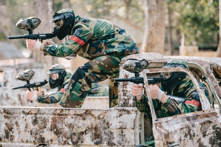 paintball team in protective masks and camouflage aiming by marker guns from broken car outdoors