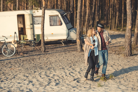 young couple with glasses of wine walking near campervan