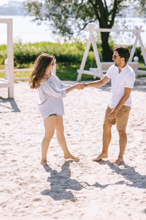 couple holding hands and looking at each other at sandy city beach