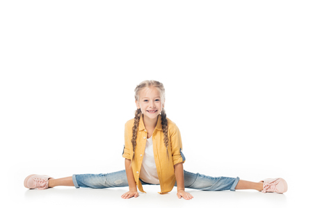 smiling little kid stretching, doing split and looking at camera isolated on white Stock Photo