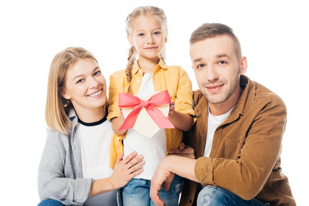 portrait of smiling parents and little daughter with heart shaped gift in hands isolated on white