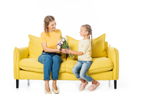 little kid giving bouquet of tulips to mother on yellow sofa isolated on white, mothers day holiday concept Foto de archivo