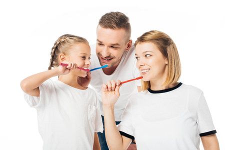 portrait of family in similar clothing brushing teeth isolated on white Stok Fotoğraf