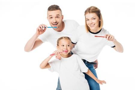 portrait of family in similar clothing brushing teeth isolated on white Banco de Imagens