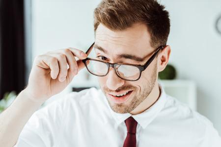 handsome smiling businessman winking in glasses