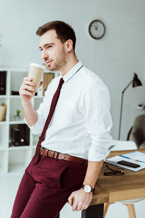 thoughtful businessman with coffee to go leaning on table in modern office Stock Photo