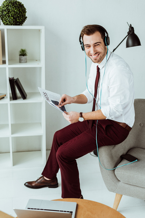 cheerful businessman listening music in headphones and reading newspaper Banco de Imagens