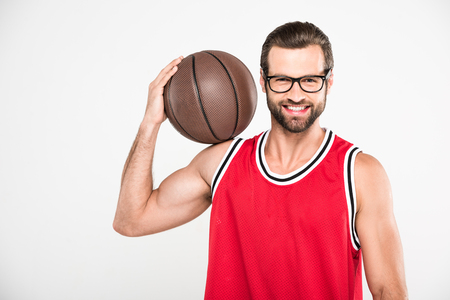 cheerful basketball player in red sportswear holding ball, isolated on white