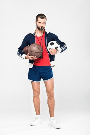 Entrenador deportivo con silbato sosteniendo pelotas de rugby, baloncesto y fútbol, aislado en blanco Foto de archivo