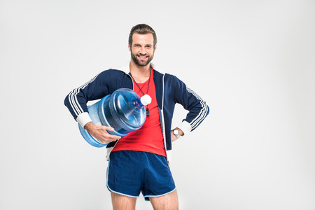 cheerful sportive coach holding big bottle of water, isolated on white