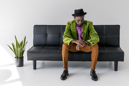 african american fashionable man in hat checking time while sitting on black sofa