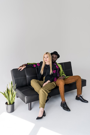 multicultural fashionable couple resting on black sofa on grey backdrop