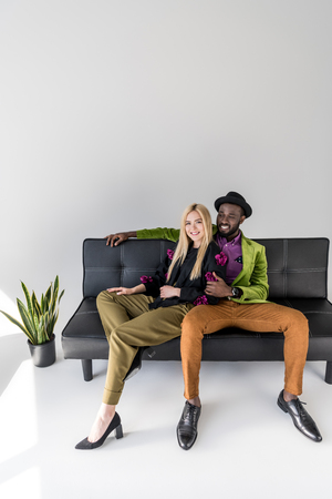 smiling multicultural fashionable couple resting on black sofa on gray background Stock Photo - 109191106