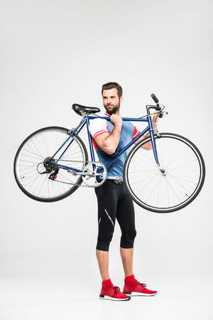handsome sportsman carrying bicycle, isolated on white