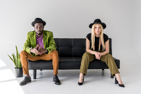 multicultural fashionable couple in hats sitting on black sofa on grey backdrop