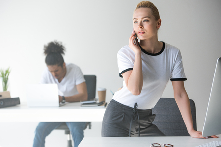 beautiful young woman talking by smartphone and looking away while leaning at table in office