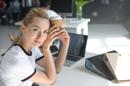beautiful young businesswoman holding disposable coffee cup and looking at camera in office Stock Photo
