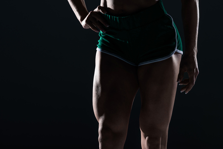 cropped view of female bodybuilder with muscular legs, isolated on black Banco de Imagens