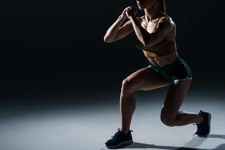 cropped view of sporty female bodybuilder doing lunges, on black Banque d'images