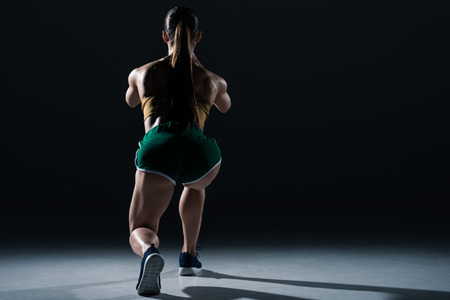 back view of muscular sportswoman doing lunges, on black