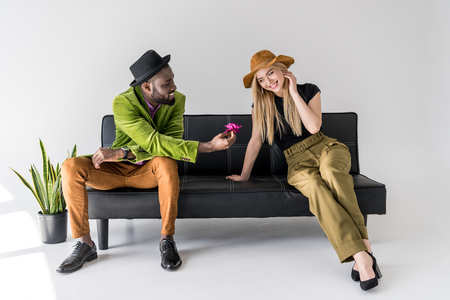 african american fashionable man presenting flower to smiling caucasian girlfriend on black sofa