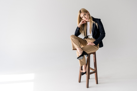 attractive young blonde woman in stylish clothes sitting on stool and looking at camera on grey