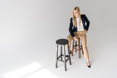high angle view of beautiful fashionable blonde girl sitting on stool and looking down on grey