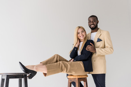 cheerful stylish young multiethnic couple smiling at camera isolated on grey