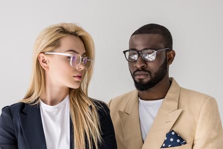 Porträt des schönen stilvollen jungen multiethnischen Paares in den auf Grau isolierten Brillen