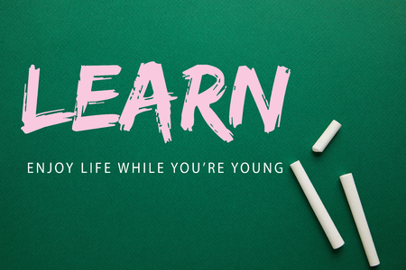 top view of white chalks on green blackboard with learn - enjoy life while you are young lettering Imagens