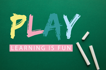 top view of white chalks on green blackboard with play - lettering is fun lettering