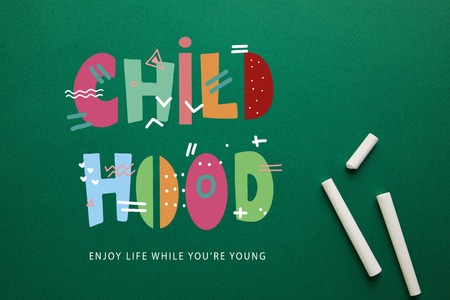 top view of white chalks on green blackboard with childhood - enjoy life while you are young lettering