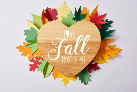 top view of wooden heart shaped board and colorful handcrafted leaves on white surface with I love fall most of all lettering