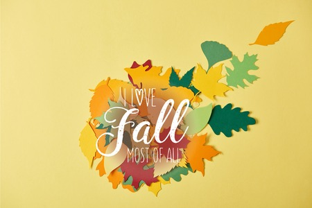 flat lay with colorful papercrafted foliage with I love fall most of all inspiration on yellow background
