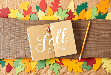 flat lay with I love fall most of all inspiration in notebook, pencil on wooden plank and colorful handcrafted paper leaves on crumpled paper background Banco de Imagens