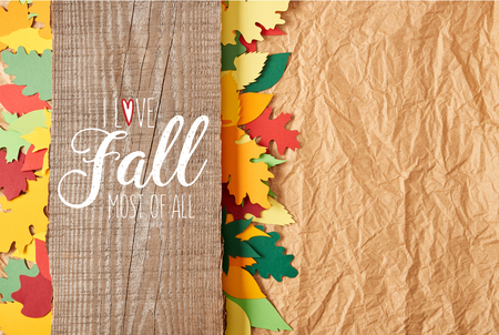top view of wooden plank with I love fall most of all inspiration and colorful paper leaves arrangement on crumpled paper backdrop Banco de Imagens