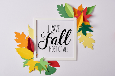 flat lay with handcrafted paper leaves and empty frame with I love fall most of all inspiration on white table