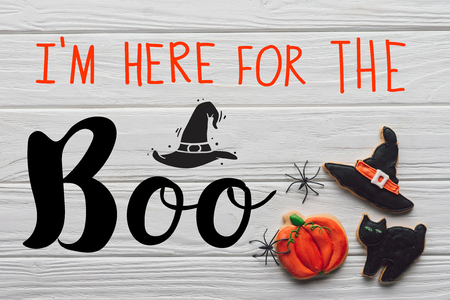 elevated view of tasty homemade halloween cookies on wooden background with Im here for the Boo lettering