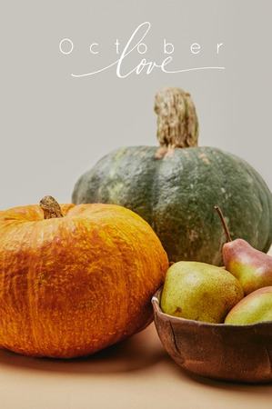 close up of autumnal harvest with pumpkins and ripe yummy pears on table with OCTOBER LOVE lettering
