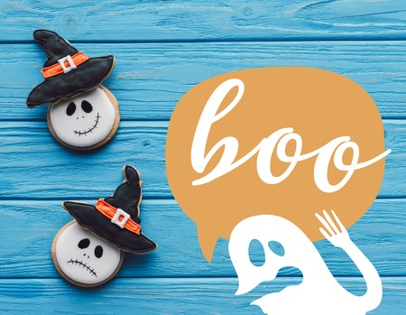 elevated view of delicious homemade halloween cookies on wooden background with ghost and