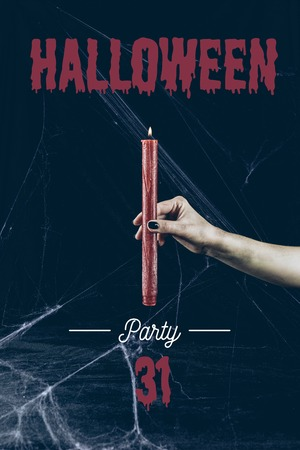 cropped view of gothic woman holding red candle in darkness with spider web with halloween party 31 lettering Stock Photo
