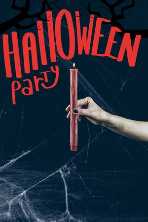 cropped view of gothic woman holding red candle in darkness with spider web with halloween party lettering
