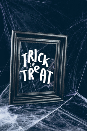black frame in spider web, creepy halloween decor with trick or treat lettering Фото со стока