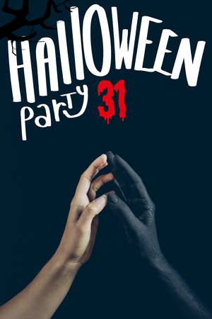 cropped view of woman touching with black demon hand isolated on black with halloween party 31 lettering