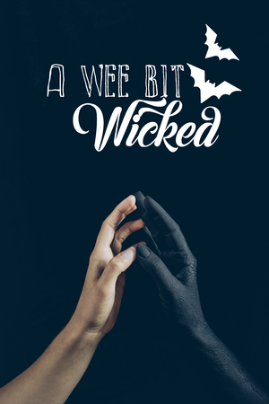 cropped view of woman touching with black demon hand isolated on black with a wee bit wicked lettering