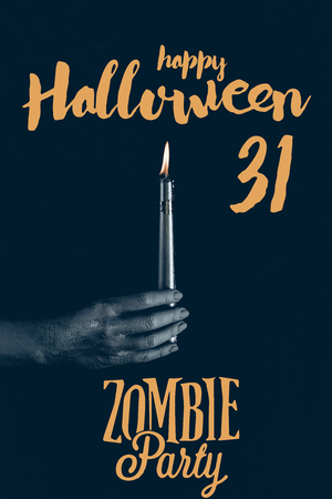 cropped view of black hand with flaming candle, isolated on black with happy halloween 31 - zombie party lettering Stock Photo